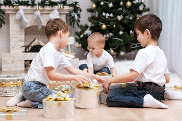 Children under the Christmas tree with gifts and toys