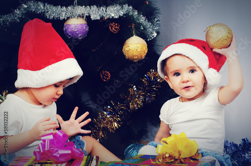 Two cute little girl sitting with gifts under the Christmas tree