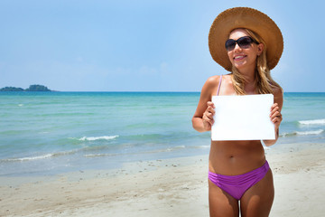 young blond woman holding blank sign at the beach