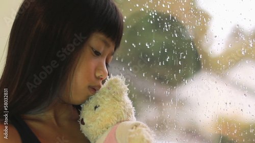 Sad Asian Girl Kisses Teddy Bear By Window