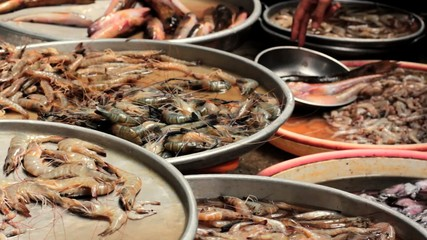 Fresh shrimps, prawns and other seafood at fish market stall