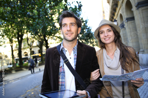 canvas print picture Couple of tourists walking in town with map and tablet