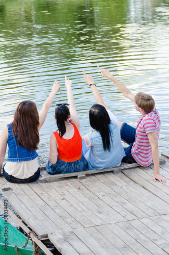 Four happy teen friends sitting on pier