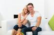 glückliches paar sitzt auf dem sofa