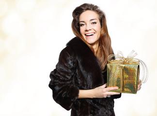 ekskluzywna dama w futrze trzyma złoty prezent