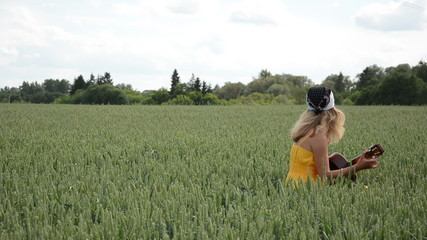 Country girl in dress and headscarf play sing guitar wheat field