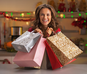 Smiling young woman with christmas shopping bags in kitchen