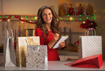 Happy young woman checking list of christmas presents