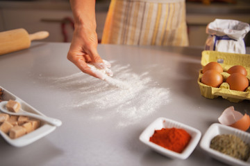 Motion blurred closeup on housewife sprinkling flour on table