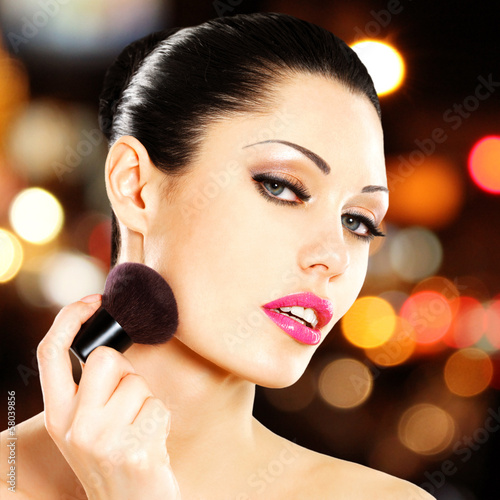 Beautiful woman applying blusher on face