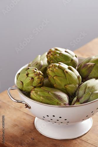 Raw pile of artichokes on colander