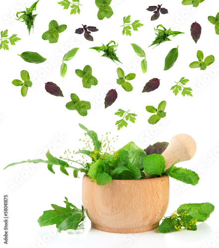 Herbs falling into mortar, isolated on white