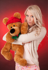beautiful blond girl holding a teddy bear