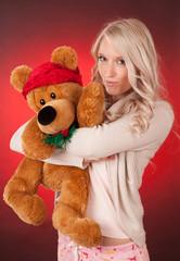 beautiful blond girl holding a teddy bear