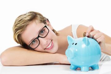 glückliche frau wirft münze in ihr sparschwein