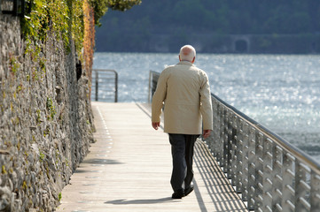 old man walking on a boardwalk