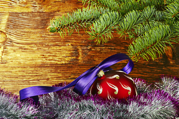 Christmas decoration. Red ball with violet ribbon, fir-tree and