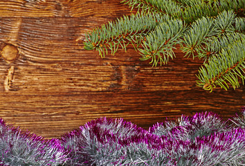 Christmas decoration. Fir-tree, tinsel and wooden background. Se