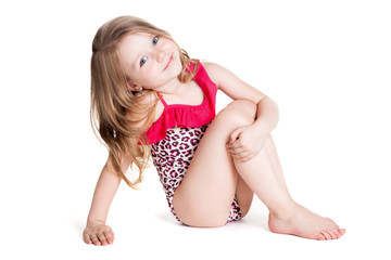 little blonde happy girl in pink swimsuit  sitting on the floor