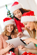 three women in santa helper hats with tablet pc