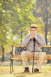 Thoughtful senior man with a cane sitting on a bench in a park