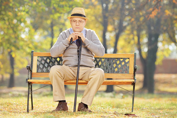 Thoughtful senior man with a cane sitting on bench in a park