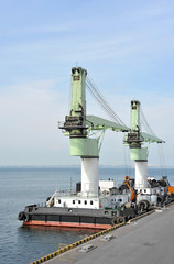Floating cargo crane over blue sky background