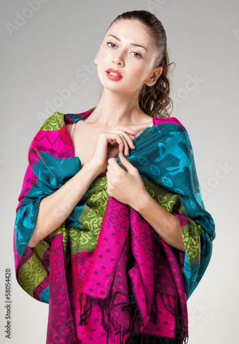 beautiful woman wearing colorful kashmir scarf isolated on grey