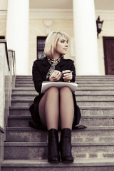 Young business woman with a notebook sitting on the steps