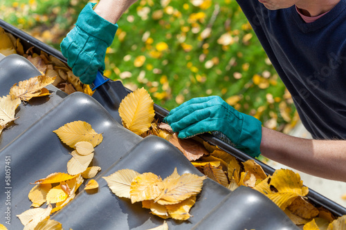 Man cleaning the gutter - 58057451