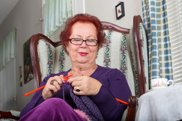 Senior Woman Relaxing while Knitting Happily