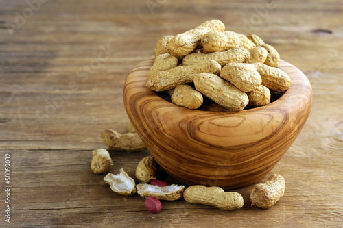 peanuts nuts in shell  in a wooden bowl on the table
