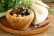 marinated green and black olives (Kalamata) in a wooden bowl