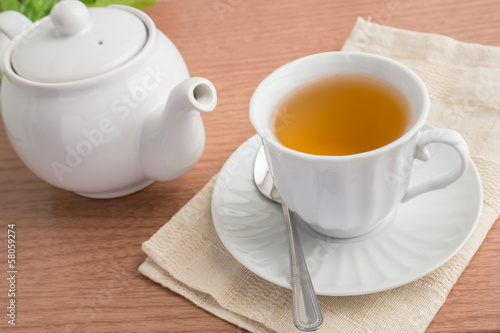 A cup of green tea and a teapot