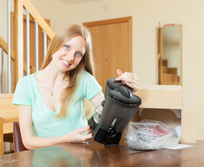 woman reading  warranty card for new coffee machine  at home int