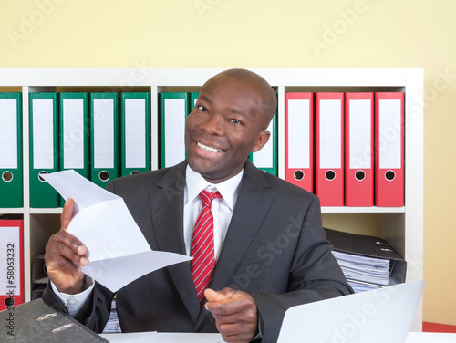 African businessman in office is happy about good news