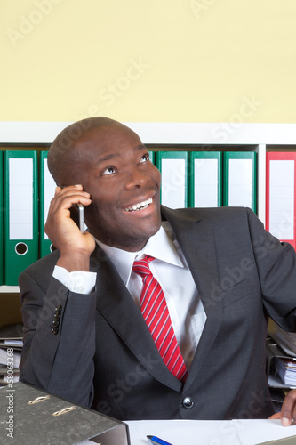 Laughing african businessman at phone