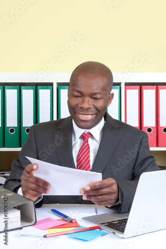 Laughing african businessman reading a message