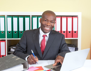 Laughing african businessman writing a message