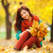 Young pretty woman relaxing in the autumn park