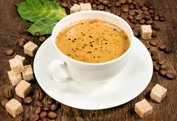 coffee on a wooden background with beans and cane sugar