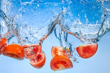 Tomato. Vegetables fall deeply under water with a big splash