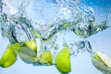 Green apples. Fruits fall deeply under water with a big splash