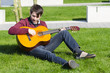 junger mann übt draußen gitarre