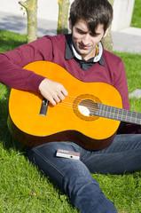 junger mann stimmt die gitarre