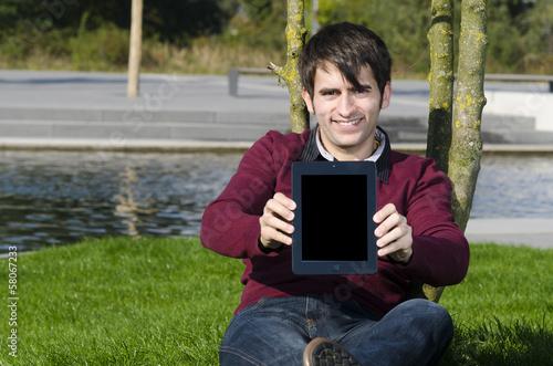 junger mann präsentiert tablet