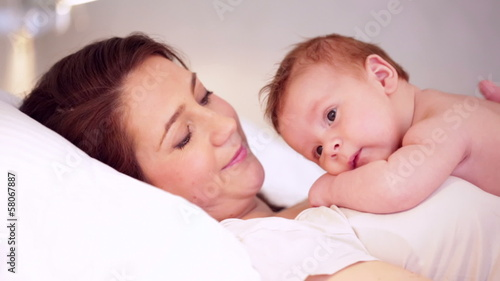 Caring mother with baby lying in bed, kissing the baby boy