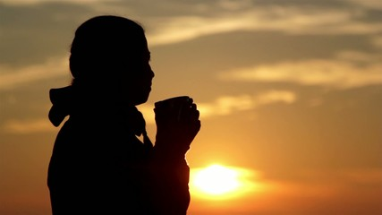 Girl drinks tea at dawn(hands up)