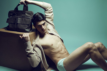 Male high fashion concept. Handsome man in underwear with bag