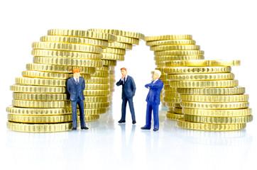Figuren neben Geldmünzen